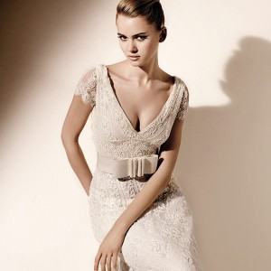 Closeup of model wearing a short cap sleeve lace wedding dress by Valentino Sposa Pronovias