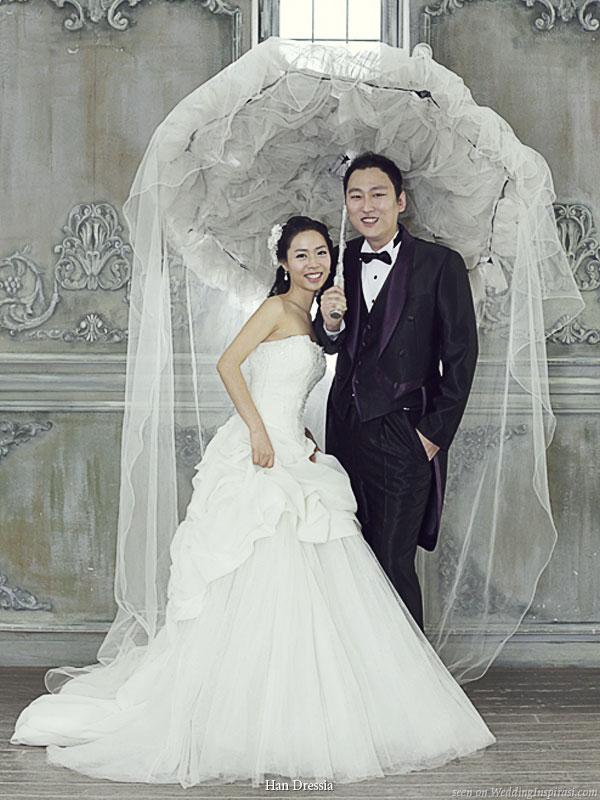 Bride and groom in wedding attire posing under a large tulle parasol umbrella
