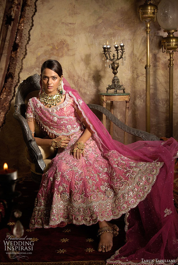 Soft pink lehnga and choli style blouse on a brocade base heavily embroidered with silver and tone on tone thread embroidery and stones.