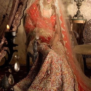 Tomato red bridal ghagra choli on muted brocade base with traditional gold zardozi thread and wire embroidery by Indian designer Tarun Tahiliani