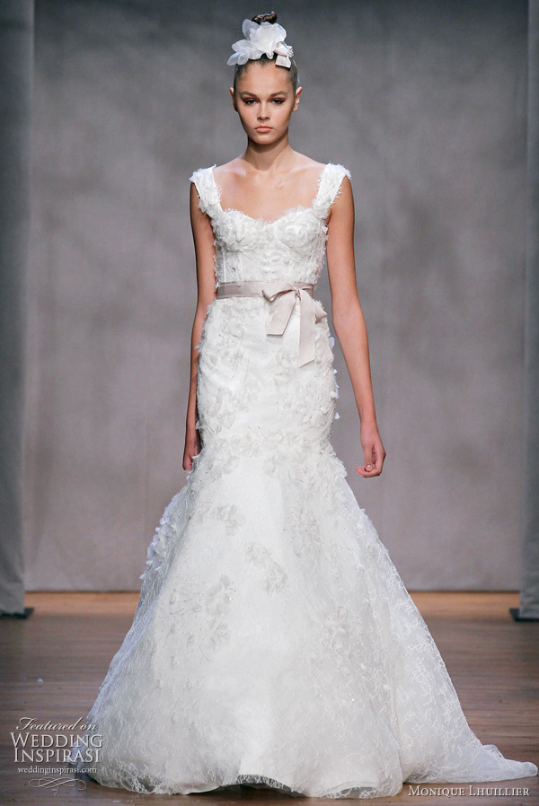 Monique Lhuillier wedding dress, Fall 2011: Aspen - ivory embellished chantilly lace elongated corset bodice gown with exaggerated trumpet skirt, embellished straps and covered   all over with organza embroidered flowers, shown with cameo hyacinth ribbon sash