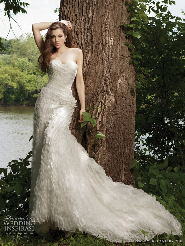 Spring 2011 wedding dress by Kathy Ireland 2be bridal - style G231120 Strapless crinkled chiffon sheath with sweetheart neckline, directionally ruched bodice, asymmetrically dropped waistline accented with hand-crafted flower, skirt with elaborately detailed accent. Removable straps included.