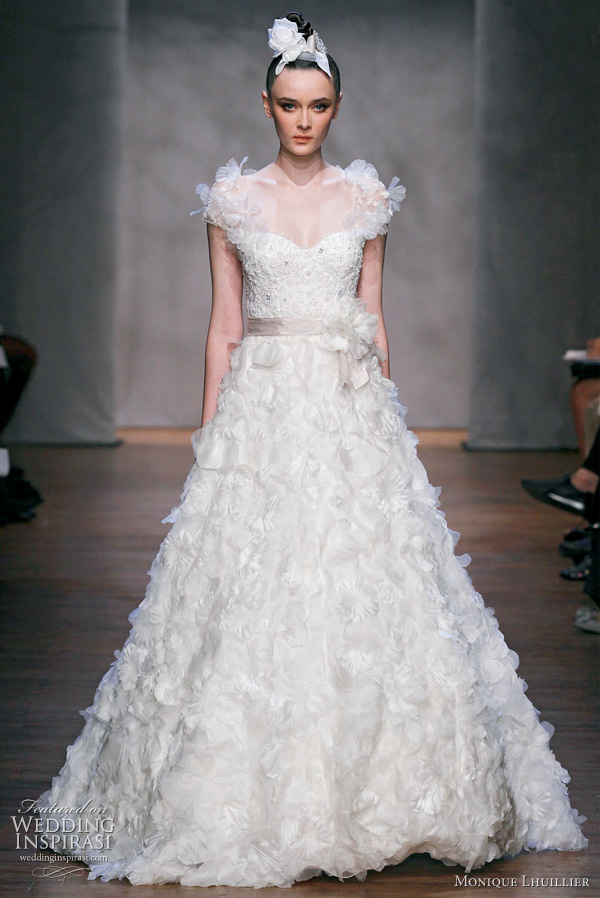 Monique Lhuillier Fall 2011 wedding dress : Dandelion - silk white embellished chantilly lace bodice with floral embroidered organza A-line skirt and embellished illusion sleeves, cameo hyacinth belt, silk white dandelion brooch
