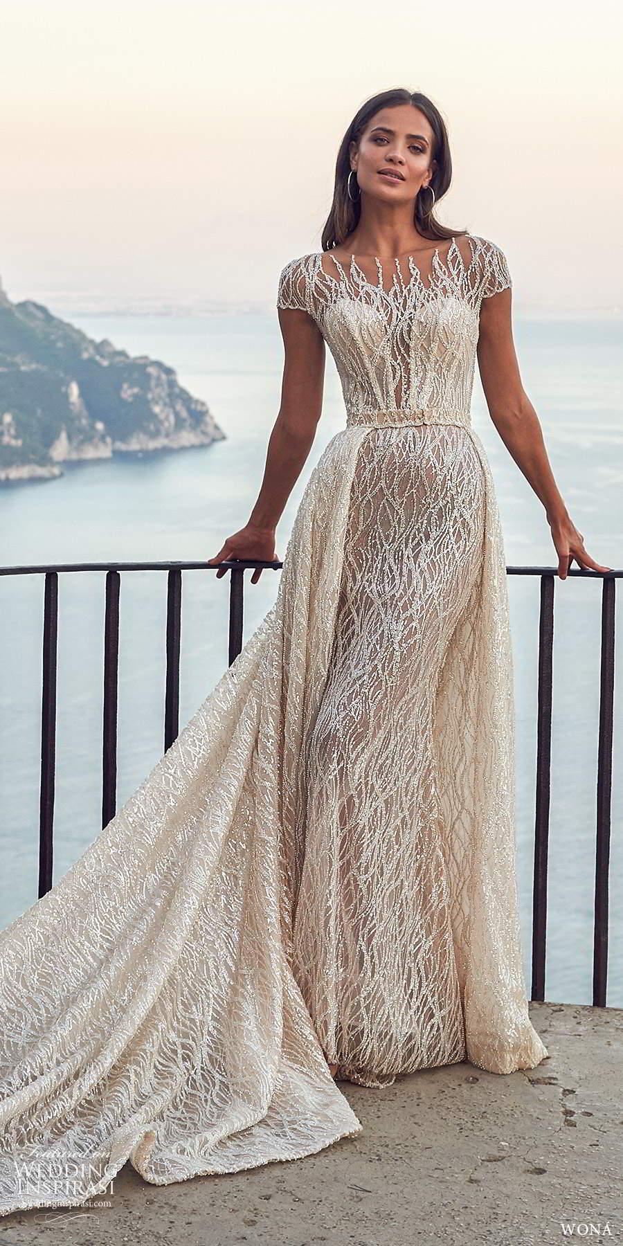 wona fall 2020 bridal illusion cap sleeves sheer bateau neckline fully embellished glitzy sheath wedding dress a line overskirt chapel train (20) mv